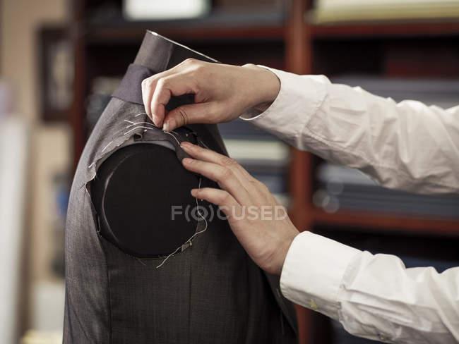 Портной закрепления одежды в традиционном магазине портных — стоковое фото
