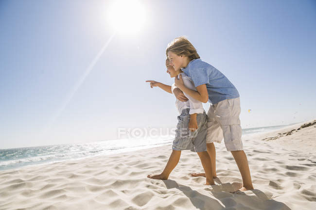 Full length side view of brothers on beach looking away at view pointing — Stock Photo