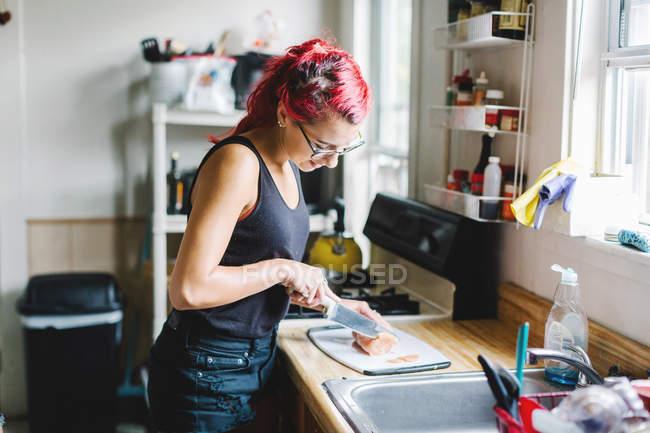Mulher nova com corte de cabelo rosa carne na cozinha — Fotografia de Stock