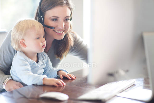 Mother and baby boy looking at computer — Stock Photo