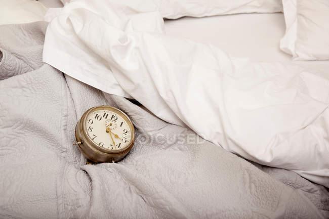 Relógio despertador na cama — Fotografia de Stock