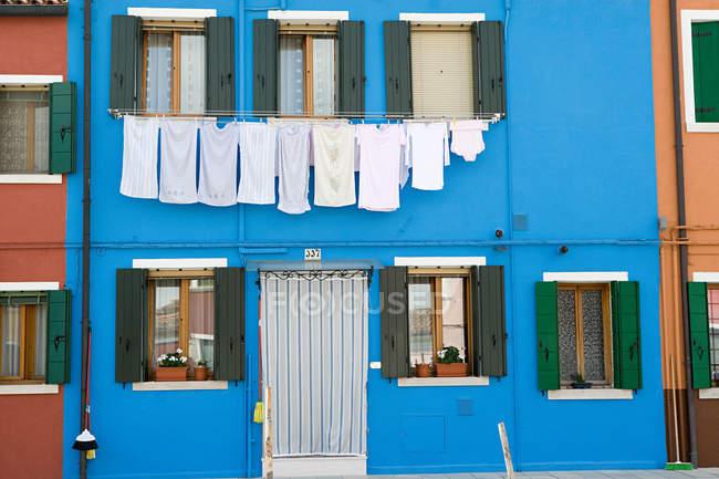 Façade de la maison bleue avec corde à linge, vue de face — Photo de stock