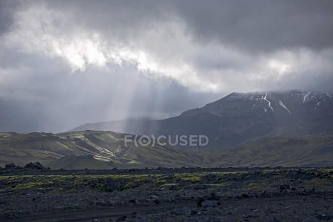 Paisagem de montanhas sob céu nublado, com raios de sol — Fotografia de Stock