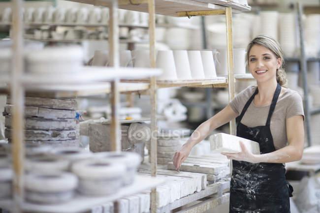 Поттер кладет глиняные блоки на полку на посудной фабрике — стоковое фото