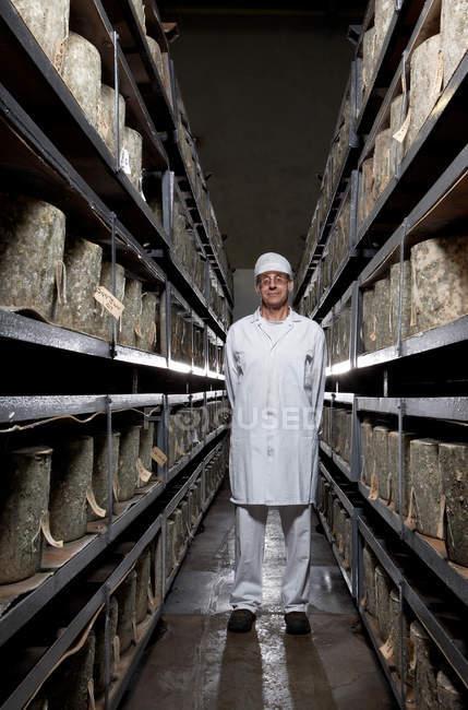 Mann steht in Lagerhalle zwischen zwei Regalen — Stockfoto