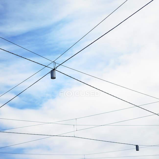Vista de ângulo baixo do céu azul e as luzes da rua com criss cruzou fios — Fotografia de Stock