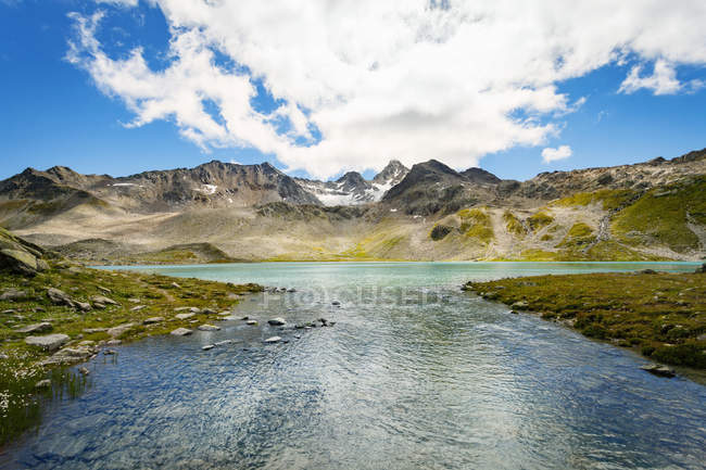 Mountain range with river under blue cloudy sky — Stock Photo