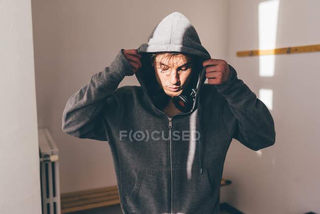 Mann im Schatten trägt Kapuzenpulli und schaut nach unten — Stockfoto