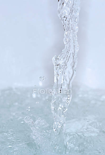 Running flow splashing into water surface — Stock Photo