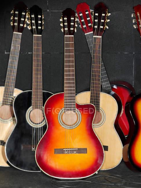 Закрыть вверх выстрел акустических гитар в строке — стоковое фото