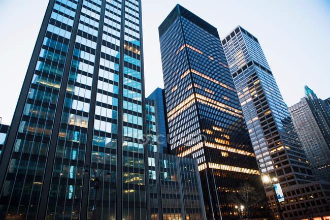 Edifícios de escritório com janelas iluminadas ao entardecer — Fotografia de Stock