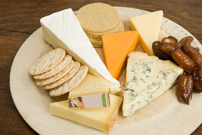 Close-up view of board with various cheese and crackers — Stock Photo