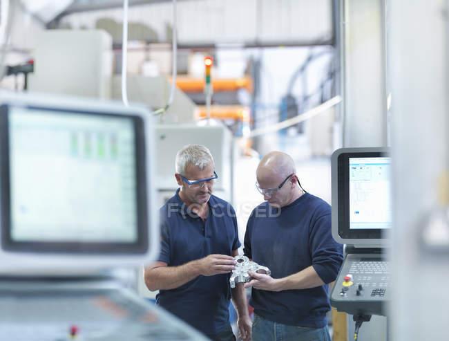 Ingénieurs inspectant le composant métallique complexe dans l'usine — Photo de stock