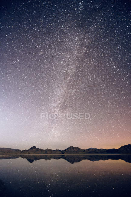 Reflecting pool of mountain range and Milky Way in night sky — Stock Photo