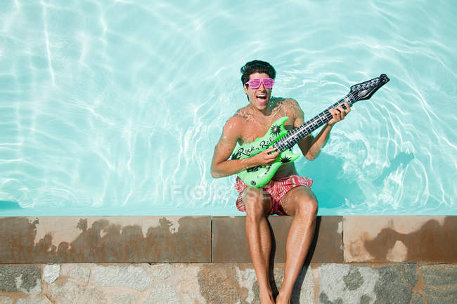 Man in pool with inflatable guitar — Stock Photo
