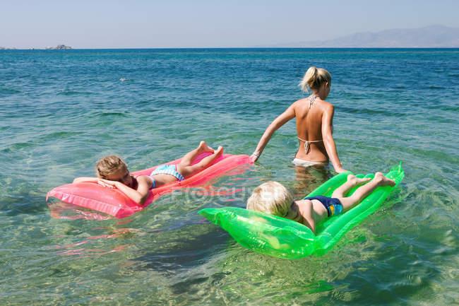 Девочка и мальчик на надувных матрацах в морской воде с мамой — стоковое фото