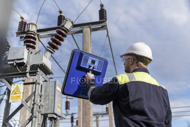 Trabalhador que usa o detetor parcial da descarga na subestação da eletricidade — Fotografia de Stock