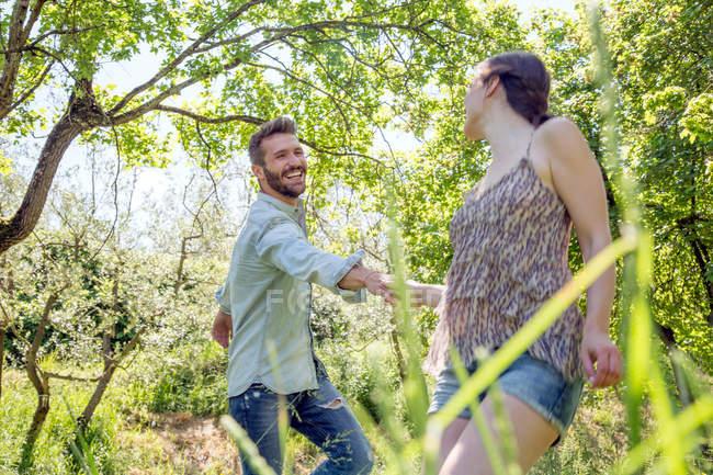 Giovani coppie che tengono le mani nella foresta scherzare sorridente — Foto stock