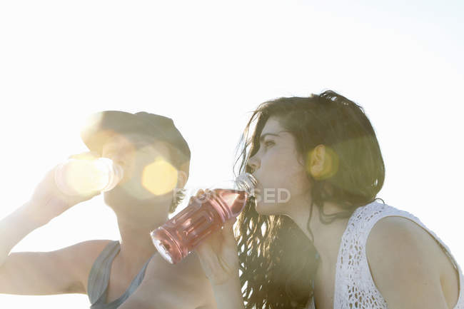 Young couple drinking soft drinks at beach — Foto stock