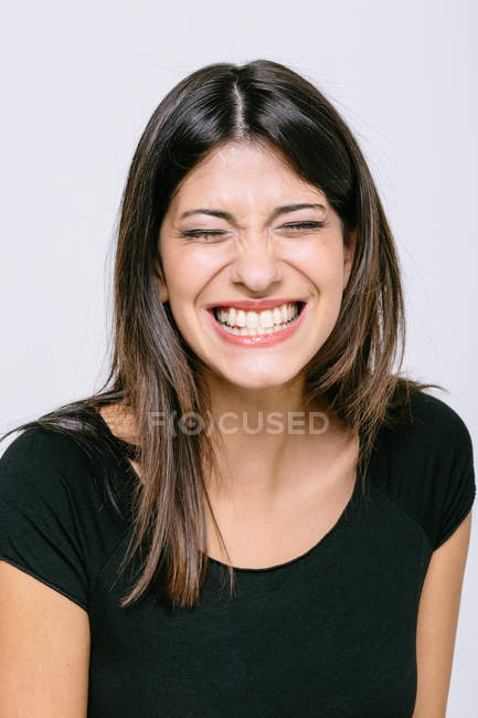 Head and shoulder portrait of young woman eyes closed toothy smile — Stock Photo