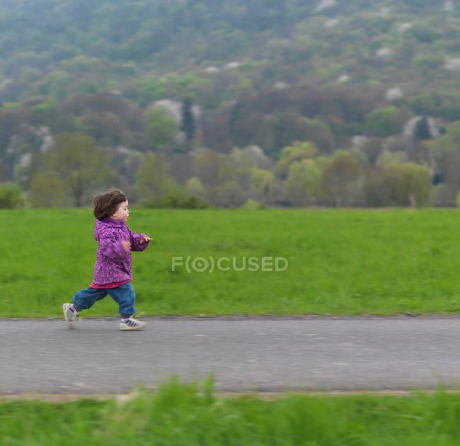 Junges Mädchen läuft Fußweg entlang — Stockfoto