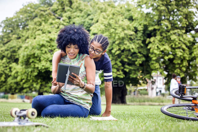 Junge und Mutter lesen gemeinsam digitales Tablet im Park — Stockfoto