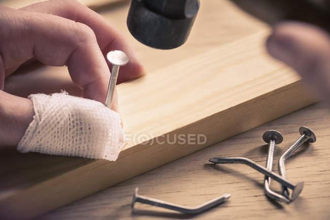 Обвязанный палец, держащий гвоздь на дереве — стоковое фото