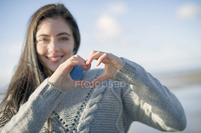 Young woman making heart shape with hands — Stock Photo