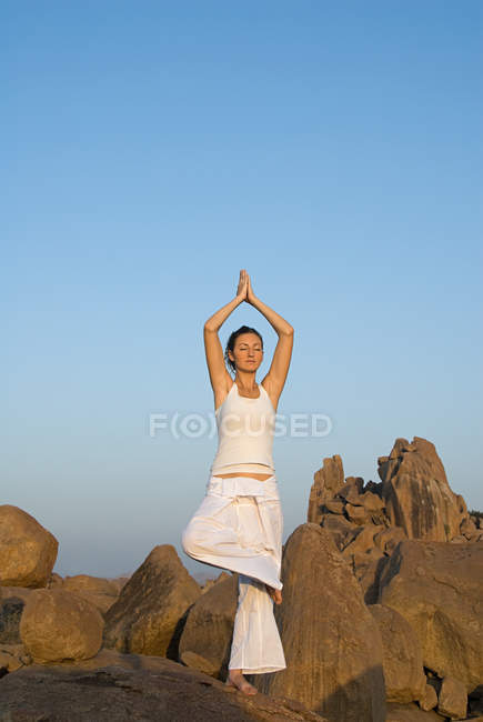 Woman in yoga pose by rocks — Stock Photo