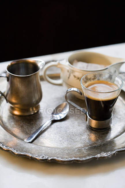 Espresso cup on tray with jugs and spoon — Stock Photo