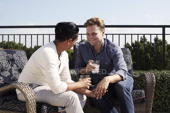 Pareja homosexual disfrutando de beber al aire libre, cara a cara cogido de la mano - foto de stock