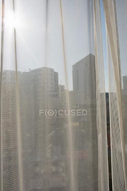Luz solar na cortina de rede e silhuetas de edifícios — Fotografia de Stock