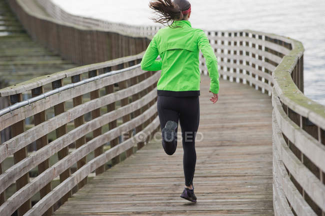 Woman running on wooden dock — Stock Photo