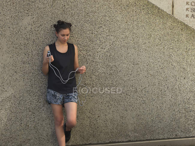 Young woman holding skipping rope against concrete wall — Stock Photo