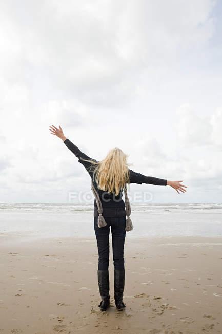 Vue arrière de la femme aux bras larges sur le littoral sablonneux — Photo de stock