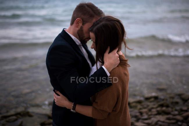 Pares adultos românticos que abraçam na praia no crepúsculo — Fotografia de Stock