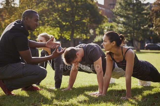 Entraîneur personnel instruisant l'homme et les femmes faisant des pompes dans le parc — Photo de stock