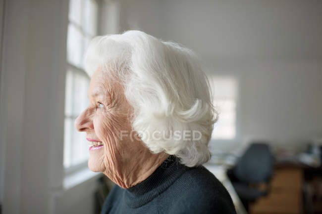 Portrait of senior woman looking out of window — Stock Photo