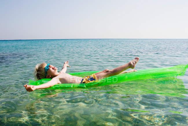 Молодий хлопець на надувному плоту відпочиваючи в морській воді — стокове фото