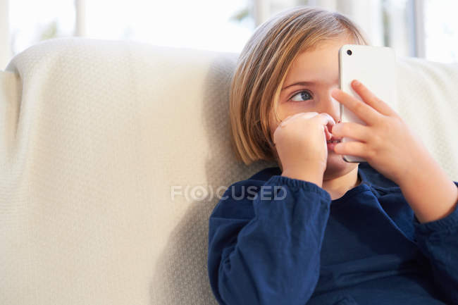 Menina no sofá usando smartphone — Fotografia de Stock