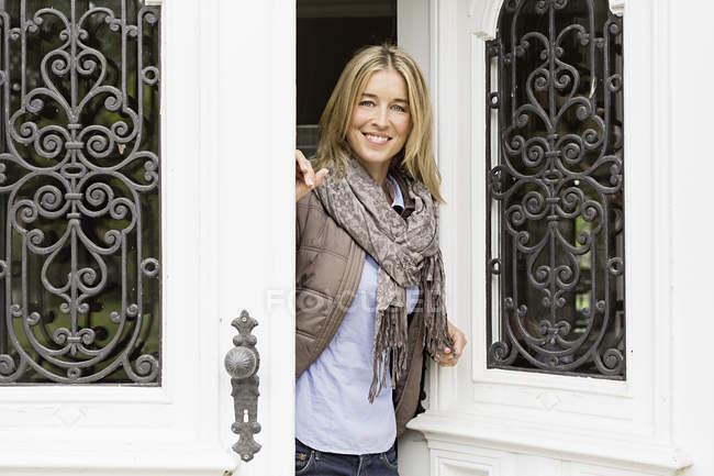 Mitte Erwachsene Frau vor Türöffnung — Stockfoto