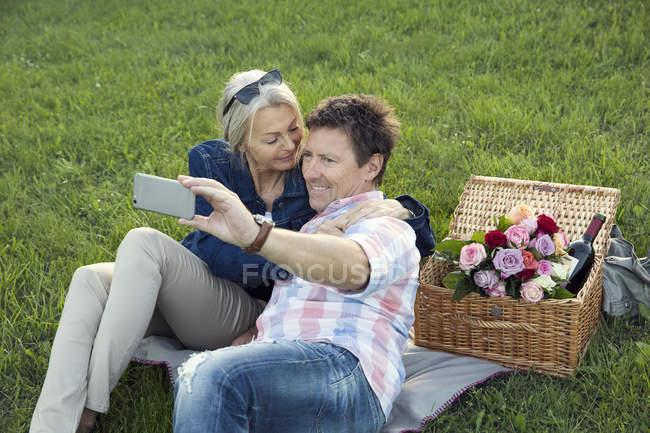 Casal maduro na grama fazendo piquenique, tirando selfie — Fotografia de Stock