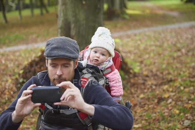 Hombre adulto medio en el parque con gorra plana llevando a su hija de vuelta en portabebés tomando selfie usando un teléfono inteligente - foto de stock