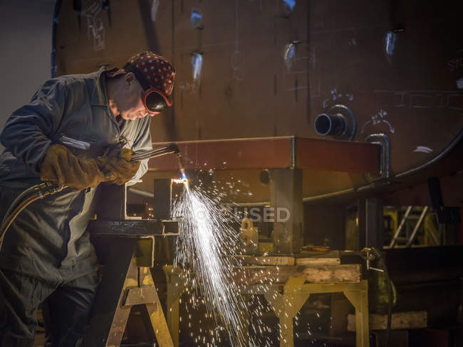 Welder using oxyacetylene torch to cut steel in factory — Stock Photo