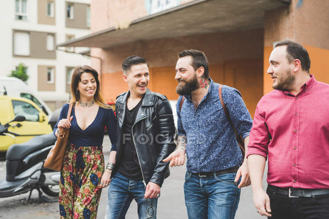 Group of friends walking on sidewalk together — Stock Photo