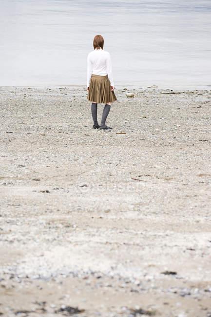 Visão traseira da mulher jovem olhando para o mar — Fotografia de Stock
