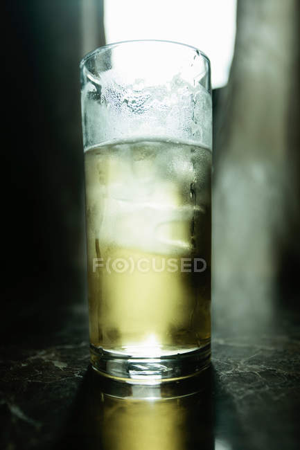Close up of glass of cocktail with ice cube — Stock Photo