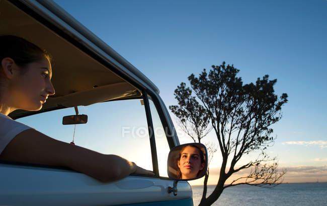 Молодая женщина смотрит из окна фургона в сумерках — стоковое фото