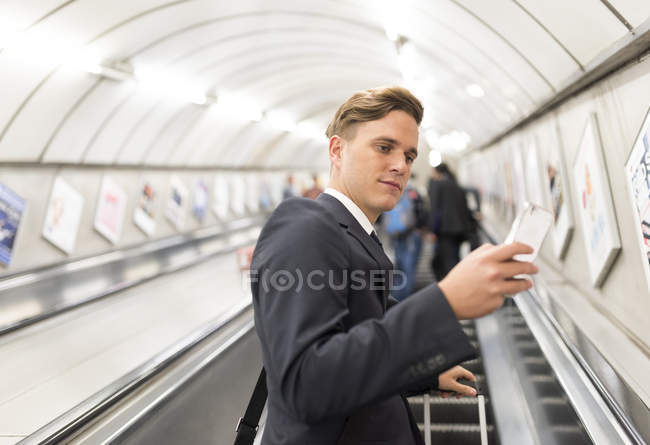 Uomo d'affari texting su scala mobile, metropolitana di Londra, Uk — Foto stock