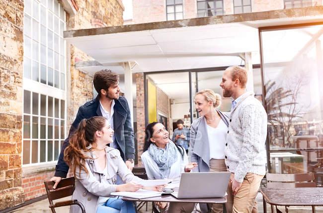 Деловые женщины и бизнесмены обсуждают это на совещании во внутреннем дворике офиса — стоковое фото